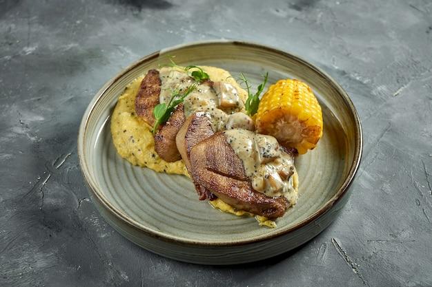 Um prato apetitoso - bife de língua de boi com molho de cogumelos, guarnecido com polenta de milho em um prato