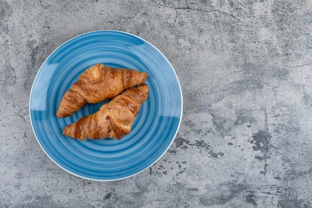 Um prato azul com dois croissants frescos simples sobre uma mesa de pedra.