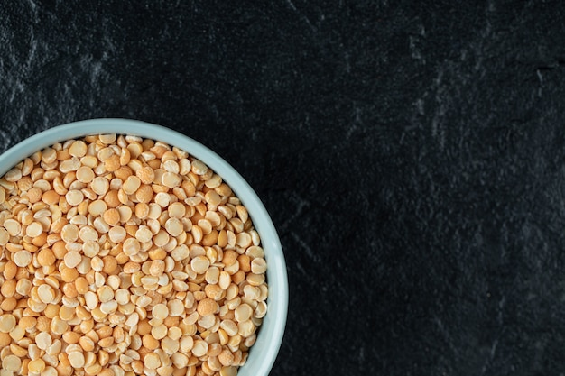 Um prato azul com lentilhas não preparadas em um preto.