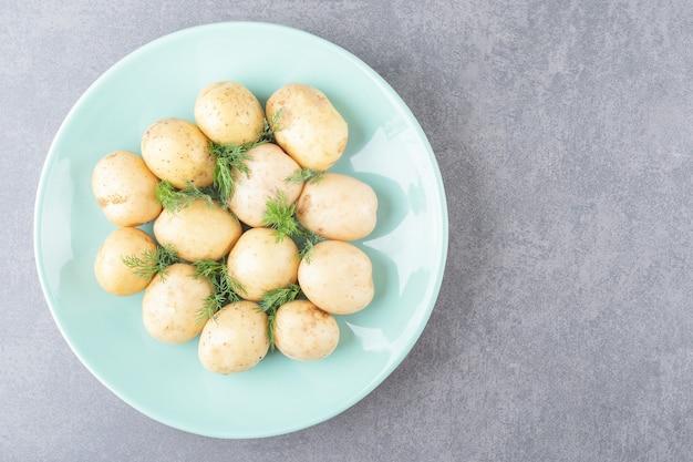 Um prato azul de batatas cozidas com endro fresco