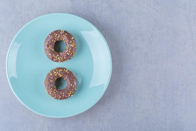 Um prato azul de deliciosos donuts de chocolate com granulado colorido.