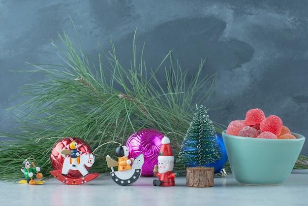 Um prato azul de geleia com pequenos brinquedos festivos de natal em fundo de mármore. foto de alta qualidade