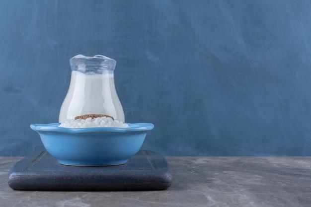 Um prato azul de mingau de aveia saudável com uma jarra de vidro de leite em uma placa de madeira.