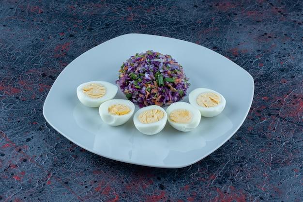 Um prato azul de ovos cozidos com legumes.