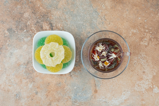Um prato branco cheio de balas de açúcar e uma xícara de chá de ervas