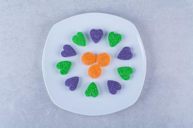 Um prato branco cheio de balas de gelatina açucaradas na superfície cinza