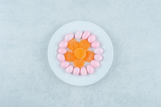 Um prato branco cheio de balas de geleia de laranja e balas rosa