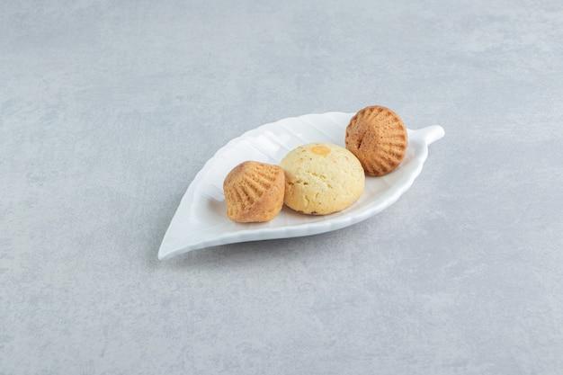 Um prato branco cheio de biscoitos doces deliciosos com açúcar.