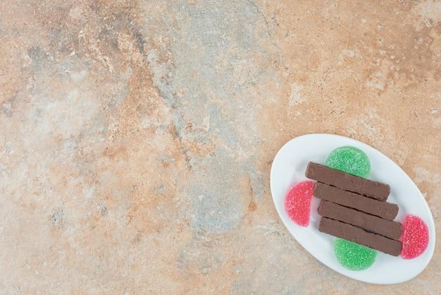 Um prato branco cheio de biscoitos e geleia no fundo de mármore