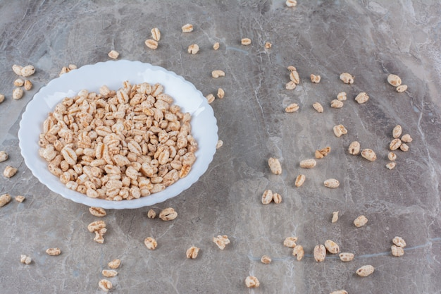 Um prato branco cheio de cereais matinais de arroz torrado.
