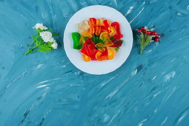 Um prato branco cheio de letras em forma de geleias doces coloridas sobre um fundo azul.