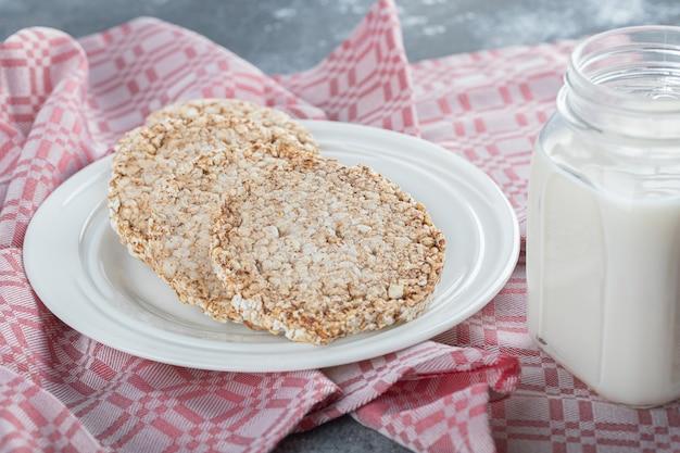 Um prato branco cheio de pão de arroz tufado com uma jarra de leite.