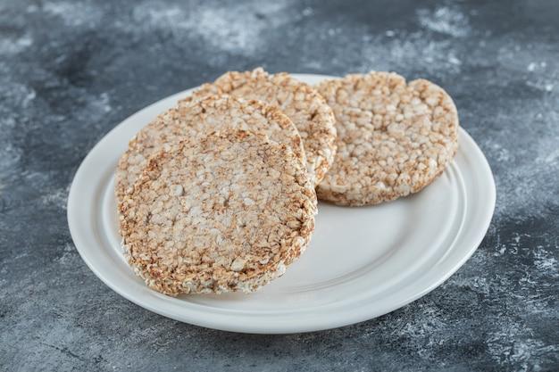 Um prato branco cheio de pão de arroz tufado sobre uma superfície de mármore.