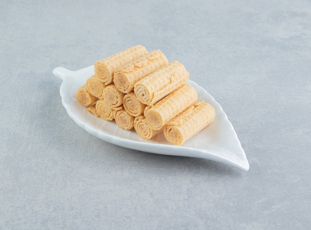 Um prato branco cheio de rolos de waffle crocantes.
