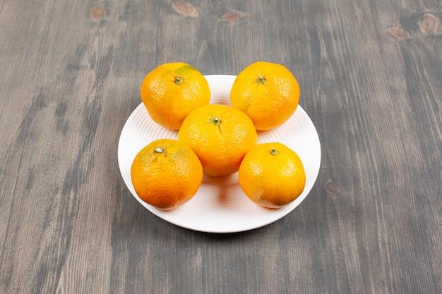 Um prato branco cheio de tangerinas frescas e doces. foto de alta qualidade