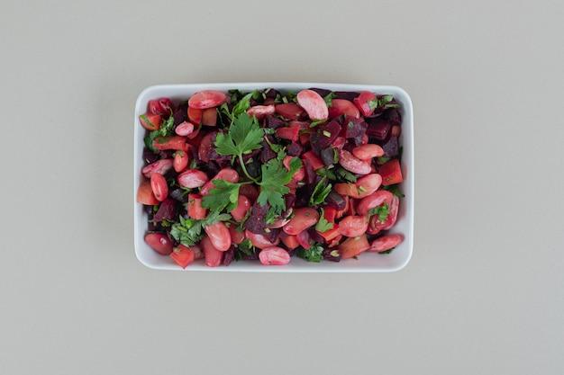 Um prato branco cheio de um delicioso vinagrete.