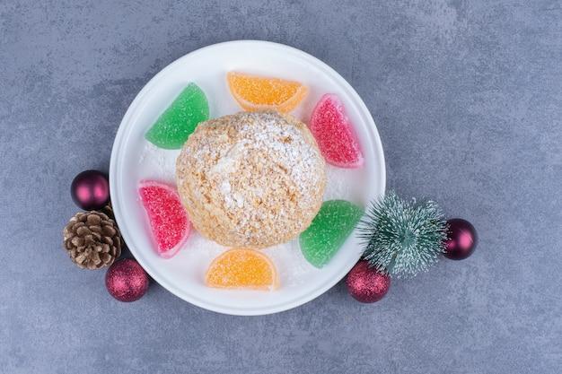 Um prato branco com biscoito e balas de geleia açucaradas