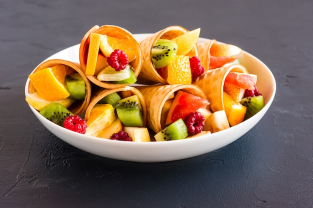 Um prato branco com cones de waffle cheios de frutas em um fundo preto.