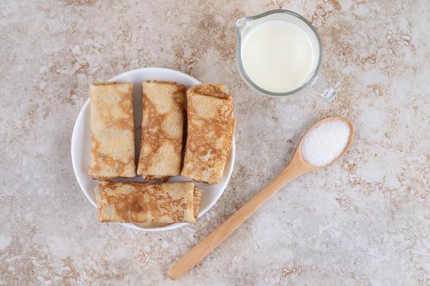 Um prato branco com deliciosos crepes doces e uma colher de pau de açúcar