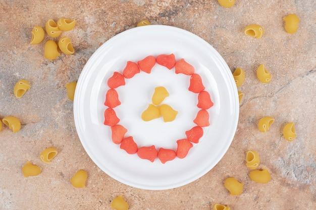 Um prato branco com macarrão cru vermelho e amarelo.