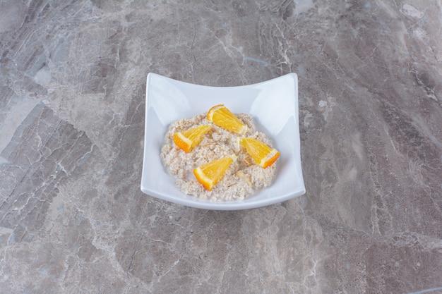 Um prato branco com mingau de aveia saudável e fatias de laranja.