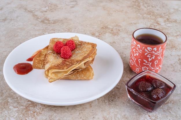 Um prato branco com panquecas e frutas vermelhas
