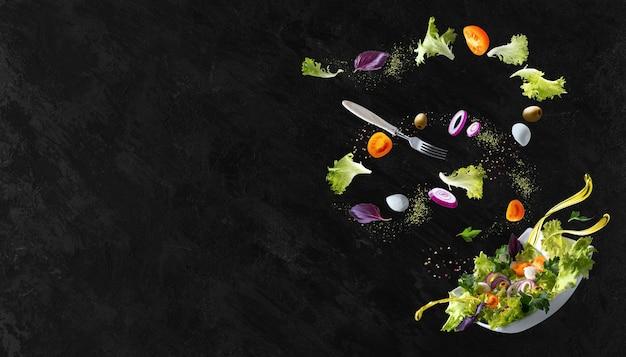 Um prato branco com salada e a flutuar no ar ingredientes: azeitonas, alface, cebola, tomate, queijo mussarela, salsa, manjericão e azeite. copie o espaço.