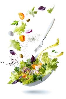 Um prato branco com salada e flutuando no ar ingredientes: azeitonas, alface, cebola, tomate, queijo mussarela, salsa, manjericão e azeite de oliva.