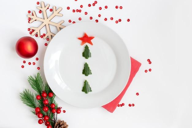 Um prato branco com um lanche de pepino na forma de uma árvore de natal e uma decoração de natal, plana leigos