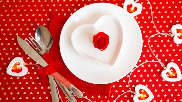 Um prato branco com uma faca e um garfo em um vermelho brilhante. placa branca em forma de coração. dia dos namorados. a vista do topo.