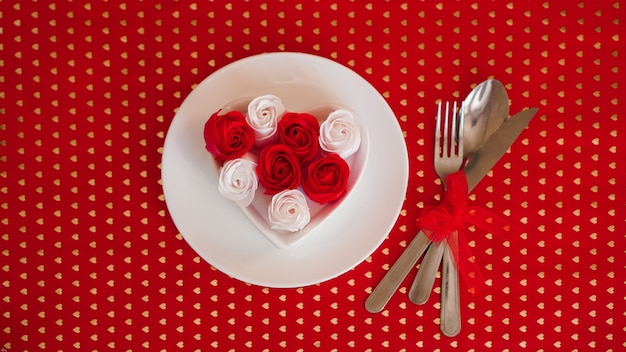 Um prato branco com uma faca e um garfo sobre um fundo vermelho brilhante. decoração de rosas vermelhas e brancas. arrumação da mesa para o dia dos namorados