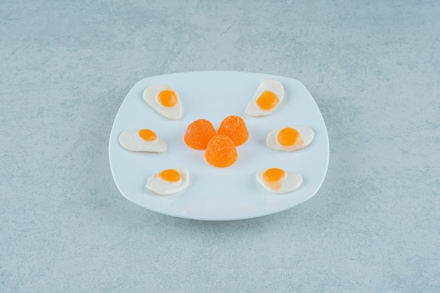 Um prato branco de balas de geleia de laranja com açúcar e doces de geleia ovos mexidos