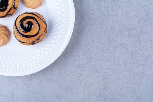 Um prato branco de biscoitos doces deliciosos com calda de chocolate.