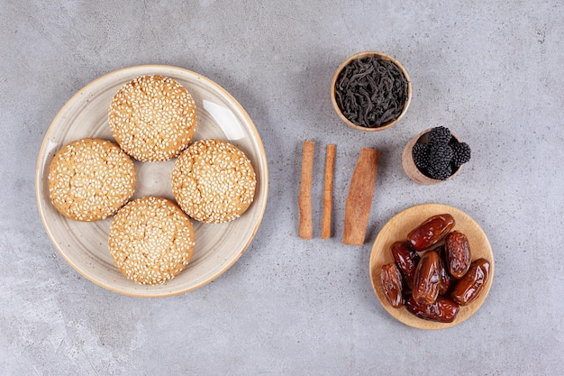 Um prato branco de biscoitos doces e tâmaras na superfície de mármore
