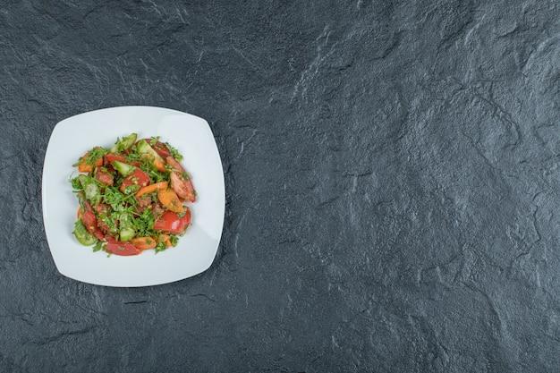 Um prato branco de deliciosa salada de vegetais.