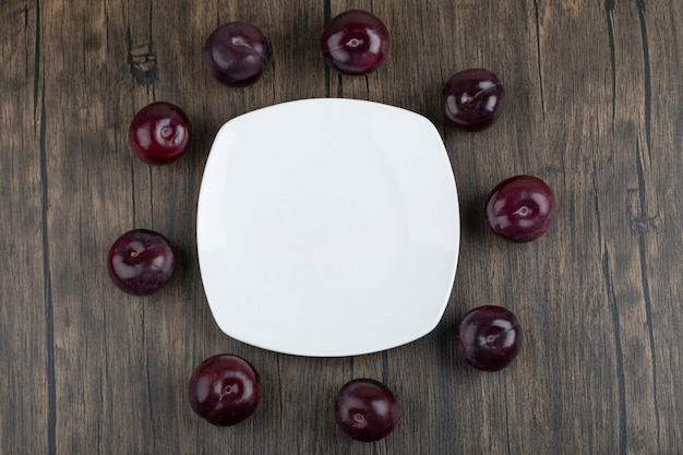 Um prato branco de deliciosas ameixas frescas na mesa de madeira.