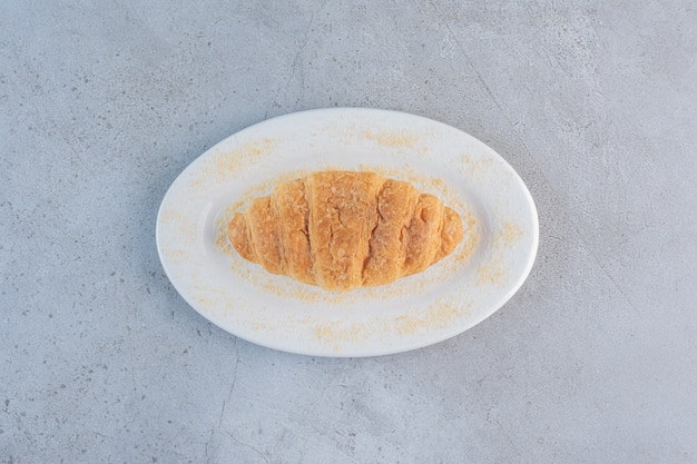 Um prato branco de delicioso croissant doce em azul.