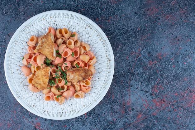 Um prato branco de delicioso macarrão com carne de frango.