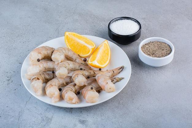 Um prato branco de deliciosos camarões com fatias de limão e especiarias em uma superfície de pedra