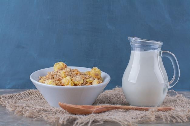 Um prato branco de flocos de milho doces saudáveis com uma jarra de vidro de leite em um saco.
