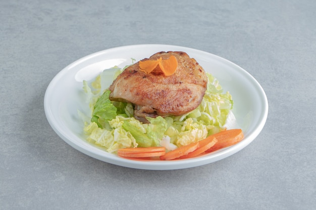 Um prato branco de frango frito, carne e cenoura fatiada.