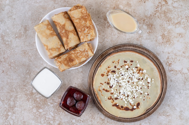 Um prato branco de saborosos crepes e geléia de morango