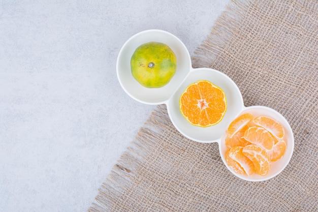 Um prato branco de tangerinas descascadas em pano de saco. foto de alta qualidade