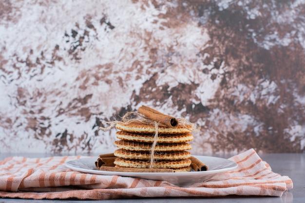 Um prato branco de waffles doces em corda com canela em pau na superfície de pedra