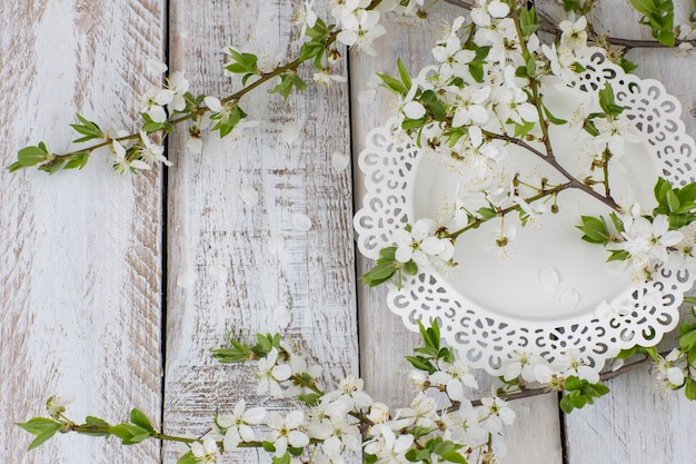 Um prato branco e um ramo de flores de cerejeira