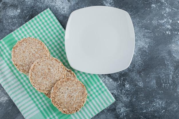 Um prato branco vazio com pão de arroz crocante sobre uma superfície de mármore.