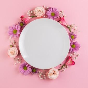 Um prato branco vazio decorado com flores coloridas contra um fundo rosa