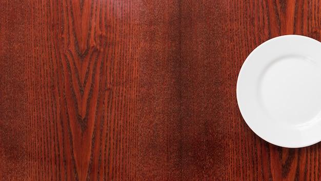 Um prato branco vazio no plano de fundo texturizado de madeira