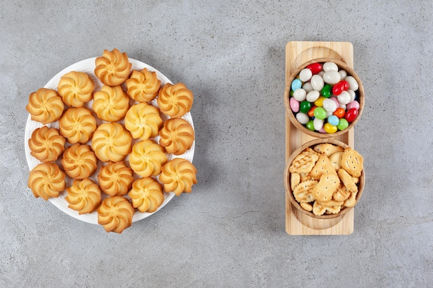 Um prato cheio de biscoitos caseiros com duas tigelas de biscoitos e doces em uma bandeja com fundo de mármore. foto de alta qualidade