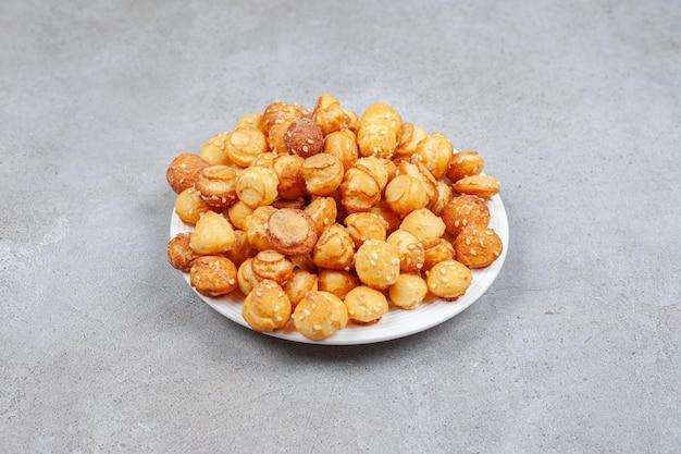 Um prato cheio de biscoitos pequenos na superfície de mármore.